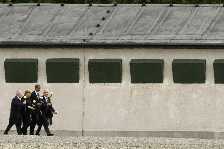 President Obama (VS) en bondskanselier Merkel (Duitsland) dragen een witte roos terwijl zij in mei 2009 luisteren naar overlevenden van concentratiekamp Buchenwald. (AP) Beeld