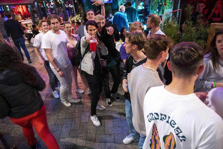 Jongeren staan in de rij om naar binnen te mogen bij een kroeg op voorlopig de laatste avond dat het tot in de kleine uurtjes door kan gaan. Beeld ANP