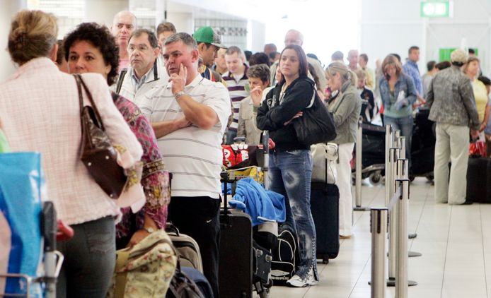 Foto ter illustratie. Lange rijen reizigers met hun bagage op het vliegveld. Ze hopen na vele geannuleerde vluchten hun ticket te kunnen omzetten of extra informatie te krijgen over het vertrek van toestellen.