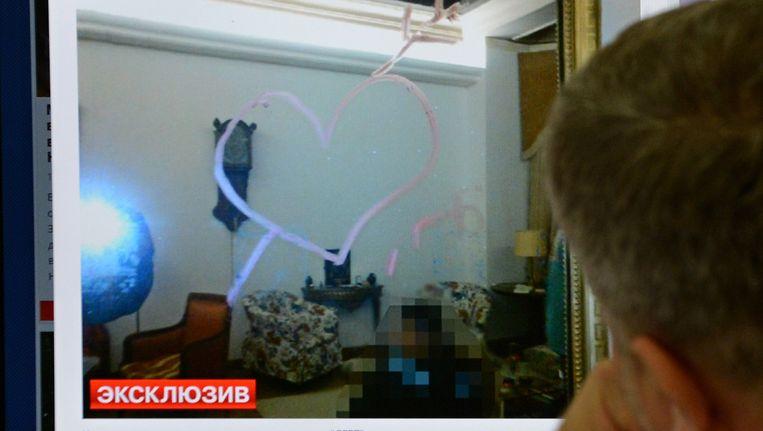 Een man kijkt op een computerscherm naar een foto van van een spiegel in de woning van Elderenbosch waar een hart met de letters LGBT (Lesbian Gay Biseksual Transseksual) op gezet. Beeld AFP