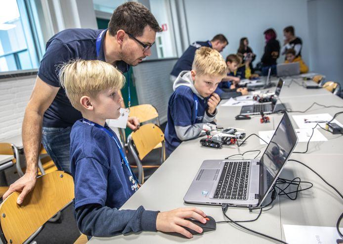 De broertjes Tobias en Florian luisteren aandachtig naar de uitleg tijdens een van de workshops programmeren op hogeschool Viaa.