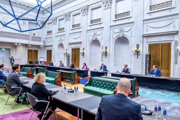 Voorzitter Chris van Dam van de parlementaire onderzoekscommissie overhandigt het rapport 'Ongekend onrecht' symbolisch aan Kamervoorzitter Arib (midden achter), in de oude zaal van de Tweede Kamer.  Links en rechts van hen leden van de commissie. Beeld Raymond Rutting / de Volkskrant