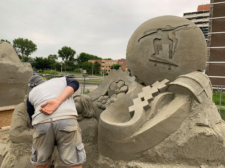 Jan Selen op de rug gezien terwijl hij aan zijn zandsculptuur werkt. Beeld Jesper Roele