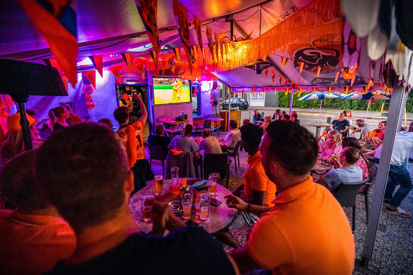 Voetbalsupporters volgen op een scherm het EK-duel tussen Nederland en Oekraïne in een café in België. In het buurland mag een flinke groep op grote schermen het EK bekijken.