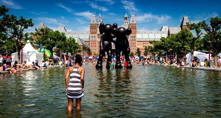 Tussen de pootjebadende toeristen kunnen kinderen lekker spetteren in de vijver op het Museumplein. Beeld ANP