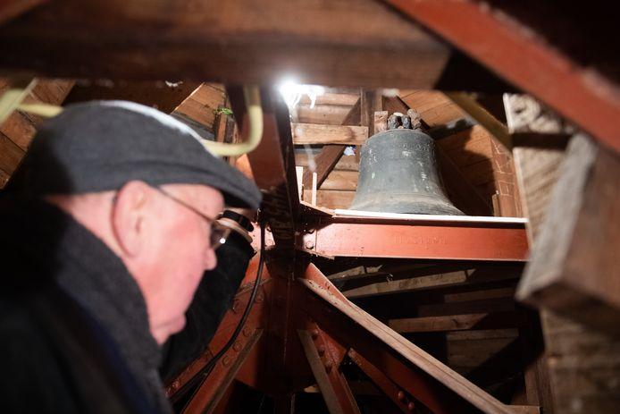 Hank -  Meneer de Bot laat de kerkklok uit 1681 zien ergens in de toren van de kerk in Hank.