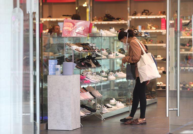 Een vrouw met mondmasker in een schoenenwinkel.