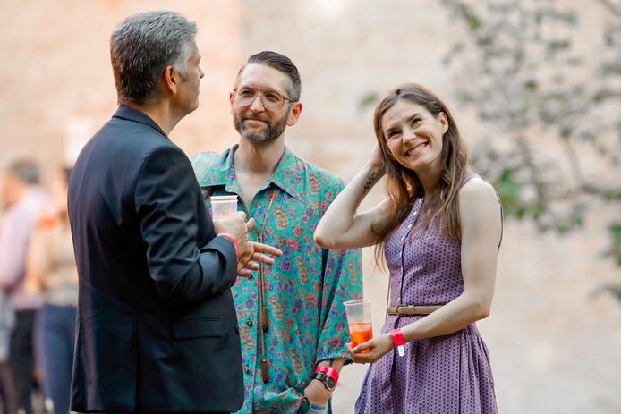 Amanda Knox met haar huidige vriend Christopher Robinson (midden) en een van de gasten op een cocktailparty op het Criminal Justice Festival in Italië.