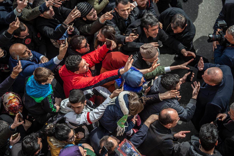 Turks president Recep Tayyip Erdogan (r.) ontmoet mensen op straat bij het verlaten van een stembureau tijdens de lokale verkiezingen in Istanbul in maart.  Beeld AFP