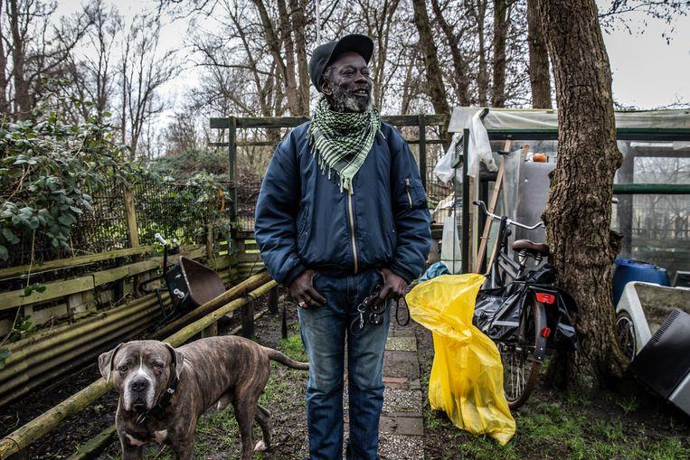 Marcel Linger, met hond Moonday, in zijn tuin die erg veel voor hem betekent. Op een langerekt stukje land aan de rand van de Bijlmerweide bevindt zich volkstuinencomplex De Vrijbuiters. Een opkoper wil de huidige tuinders weghebben om er keurige nieuwe tuinen aan te leggen.  Beeld Dingena Mol