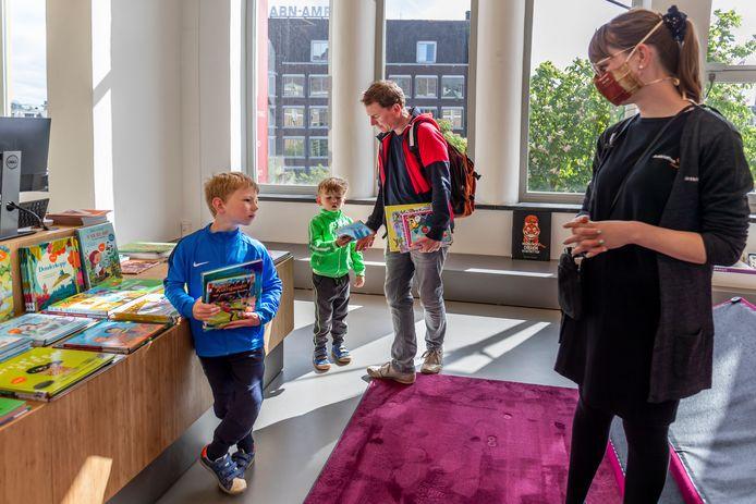 Niek en Tom (rechts) kiezen met vader Peter in hun kielzog in een razend tempo hun leenboeken uit.