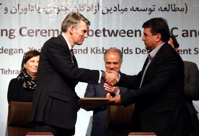 Hans Nijkamp (links), vice-president bij Shell, schudt de hand van Nouredin Shahnazizadeh, directeur van de Iranian Petroleum Engineering and Development Company (PEDEC) in 2016 Beeld EPA