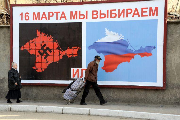 Een poster in Sebastopol, op de Krim. Er staat: op 16 maart kiezen we voor ... of ... Beeld AFP