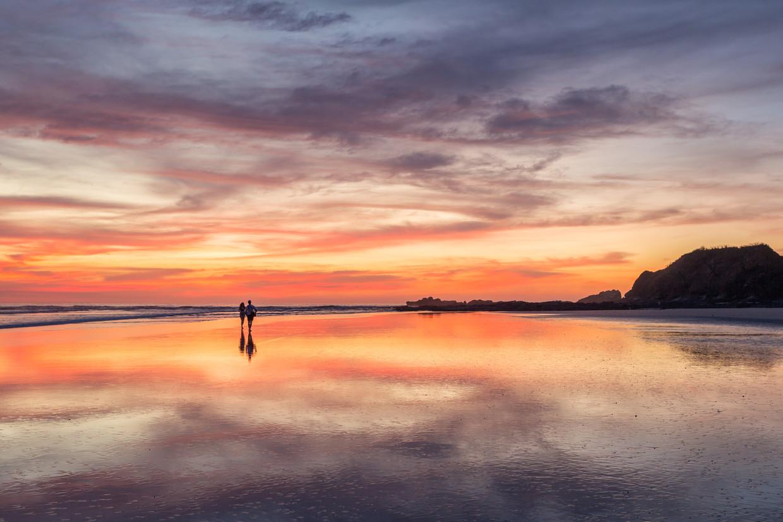 Couple walking on beach at sunset, Playa Guiones, Nosara, Guanacaste, Costa Rica