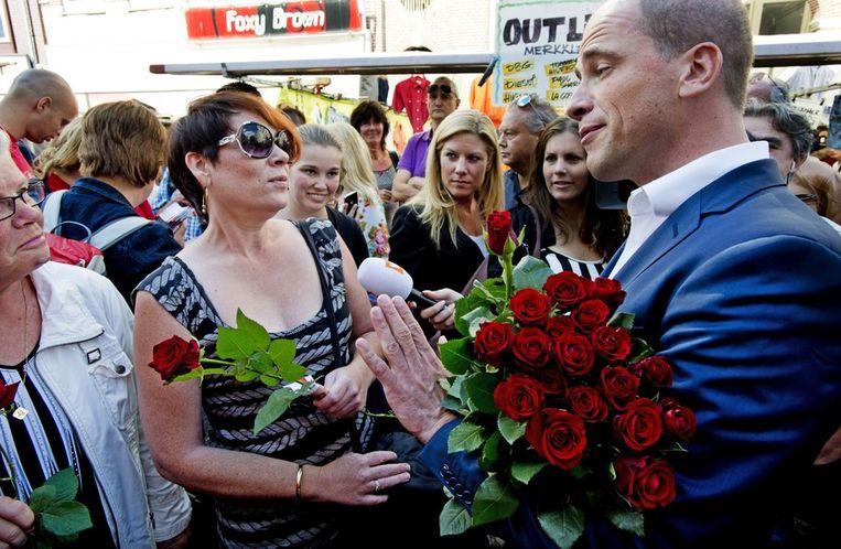 PvdA-lijsttrekker Diederik Samsom deelt rozen uit op de Albert Cuyp-markt. Beeld anp