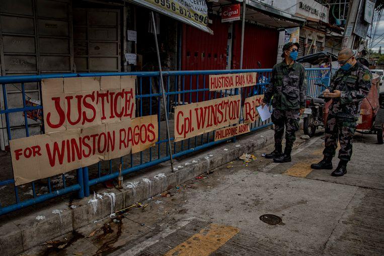 Twee Filippijnse agenten bij protestborden ter ere van Winston Ragos, een legerveteraan die door de politie werd doodgeschoten op straat. Beeld Getty Images