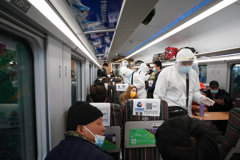 Treinpassagiers in Xinjiang worden gecontroleerd op temperatuur en testbewijzen. Beeld Getty