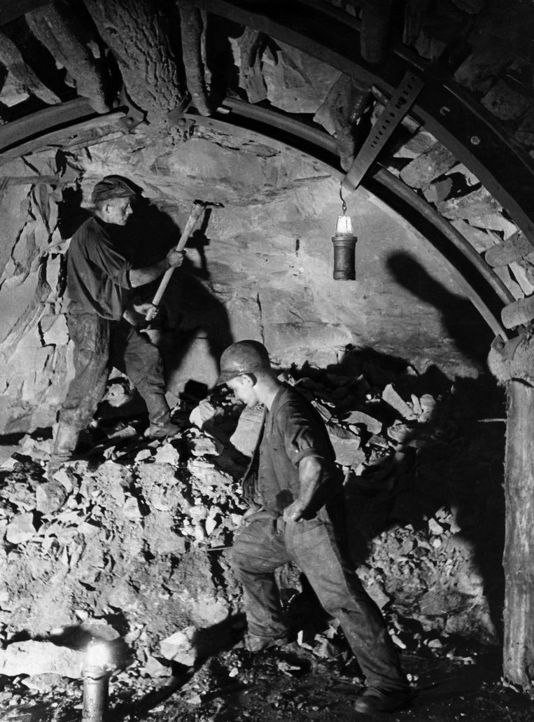 A man looking in the escape passageway of a mine - 1937-  Beeld Getty Images