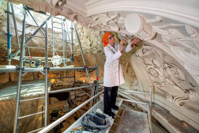 Karin Keutgens aan het werk in de koepel van kasteel Middachten. Ze staat op een hoge steiger.