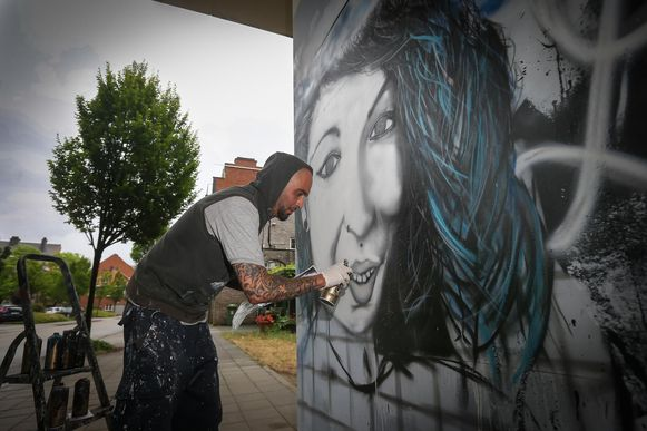 Rafaël Bouzar werkt aan het portret van Luana op een van de brugpijlers van de Westerring.