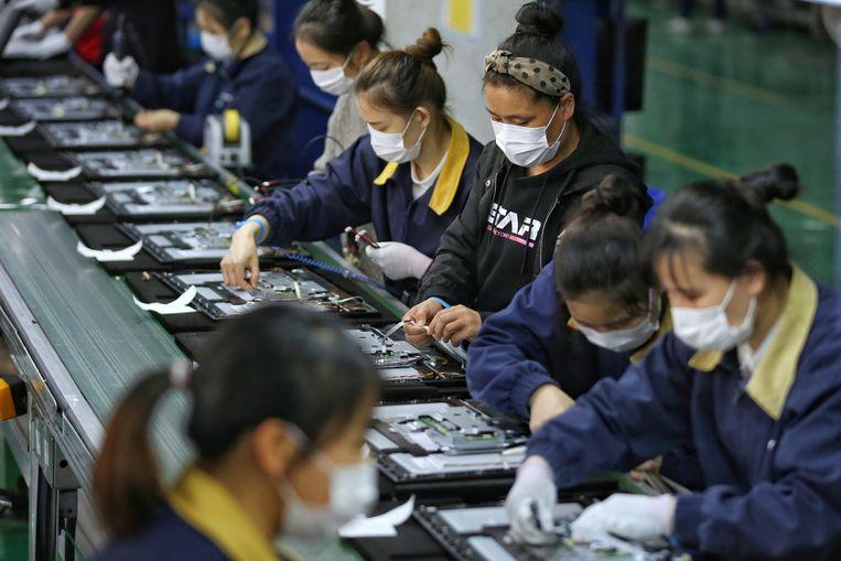 Werknemers van televisiemaker TPV zijn weer druk bezig aan een lopende band in Wuhan.  Beeld REUTERS