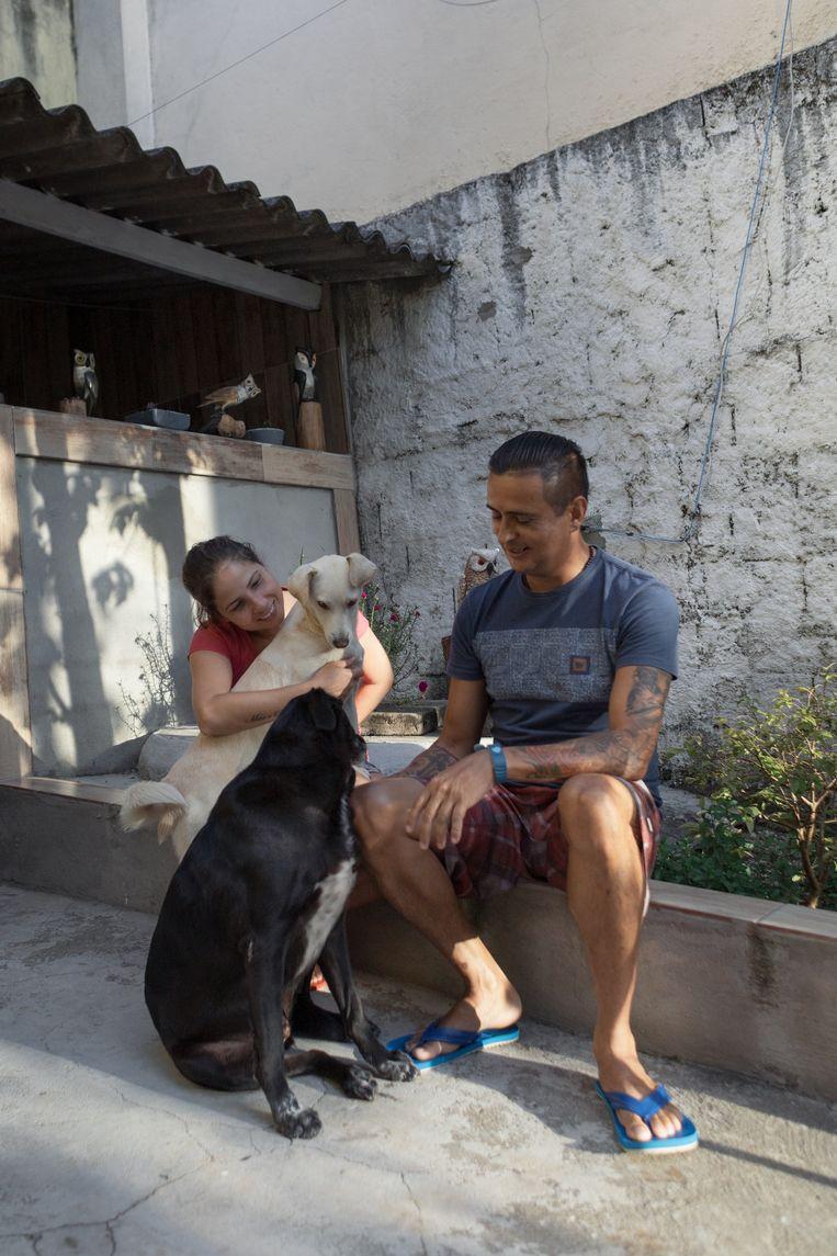 Edson Barbosa en zijn vrouw en honden voor hun huis in Jardim Novo Mundo, São Paulo. Beeld Gabriela Portilho