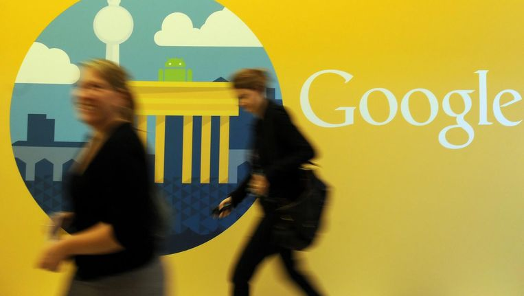 Twee vrouwen lopen langs het Google-logo in het kantoor in Berlijn. Beeld anp