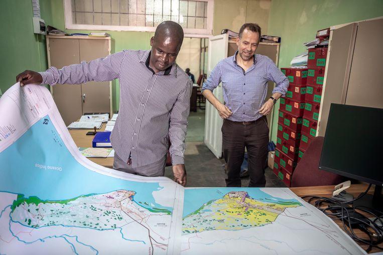 Alberti Mpango, hoofd stadsplanning van de gemeente Beira, bekijkt samen met de Nederlandse Peter van Tongeren kaarten waarop een masterplan is ingetekend om de stad klimaatbestendig te maken. Nederland heeft zich al jaren geleden gecommitteerd aan dit masterplan en toegezegd de benodigde expertise te leveren. Beeld Sven Torfinn