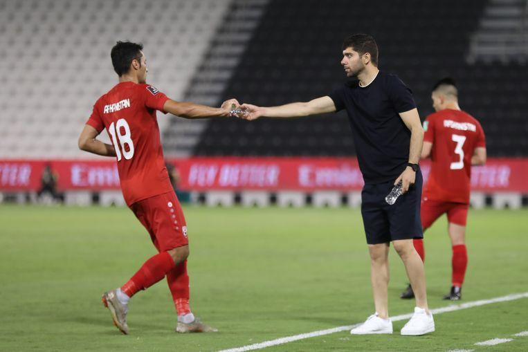 De Nederlandse bondscoach Anoush Dastgir reikt een speler een flesje water aan tijdens de wedstrijd tegen Bangladesh in Doha, Qatar. Beeld Shams Amini / AFF