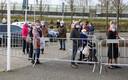 Buiten de sporthal vormt zich een lange rij wachtenden.