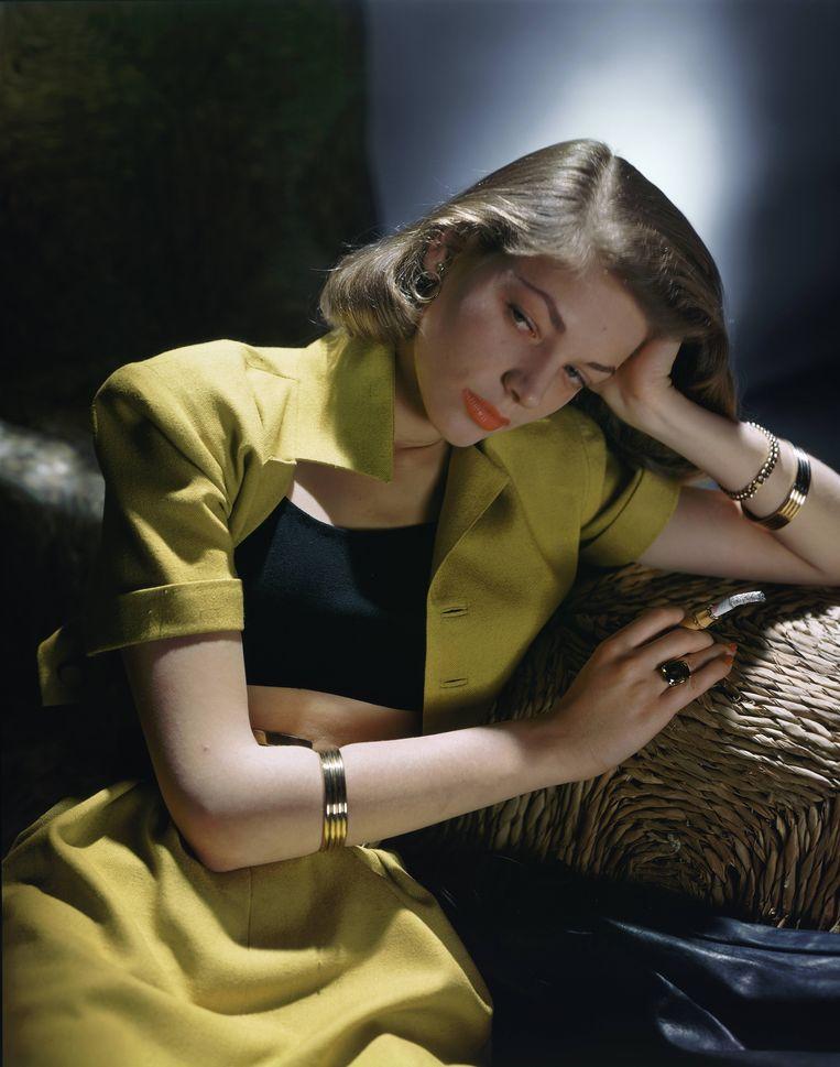 Lauren Bacall in een stijlvol mosterdgeel ensemble van B. H. Wragge.  Beeld Condé Nast / Getty Images