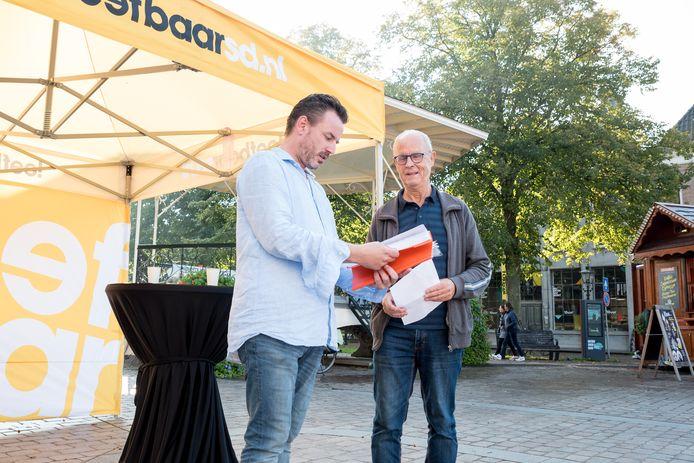 Dick Doeswijk (rechts) overhandigt aan Robbert Lievense van Leefbaar Schouwen- Duiveland een boekje om de politiek te overtuigen voor een veiliger Jannewekken.
