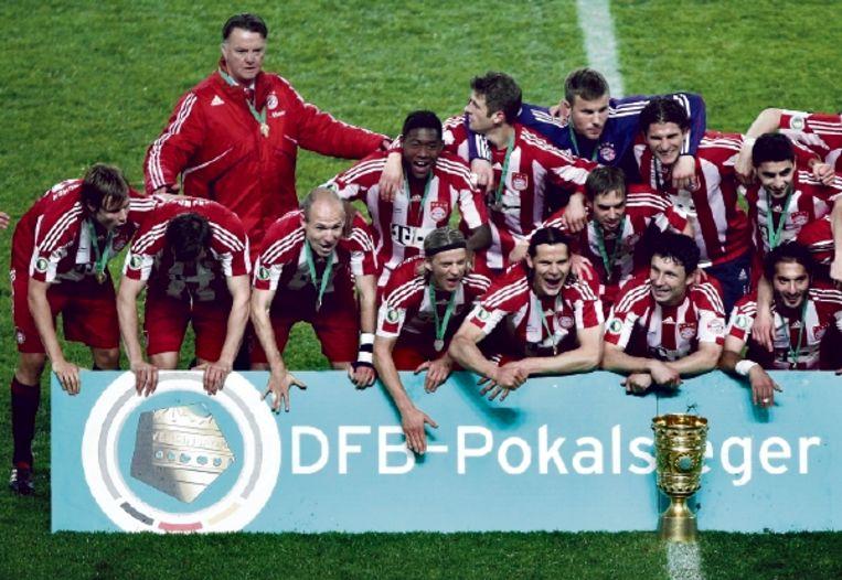 Louis van Gaal poseert met zijn feestende spelers na de 4-0 zege in de bekerfinale op Werder Bremen. (FOTO REUTERS) Beeld