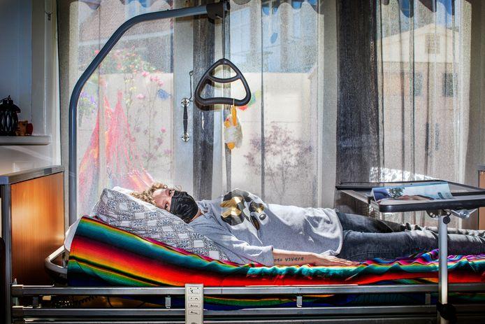 Linda van der Horst ligt in een ziekenhuisbed in haar woonkamer te wachten op medische behandeling.