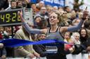 Susan Krumins gaat als eerste vrouw over de finish tijdens de Zevenheuvelenloop.