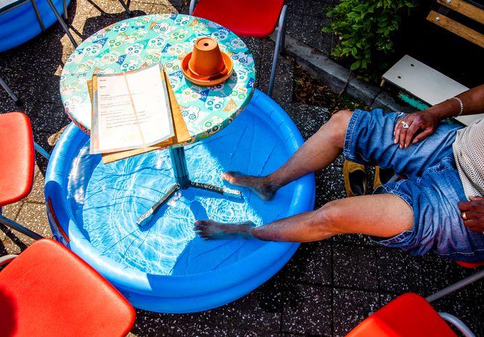 Een bloedhete dag in juli tijdens de hittegolf vorig jaar: een man zit met zijn voeten in een zwembadje op een terras in Amsterdam. Het was met 35 graden nog nooit zo warm geweest in de stad.