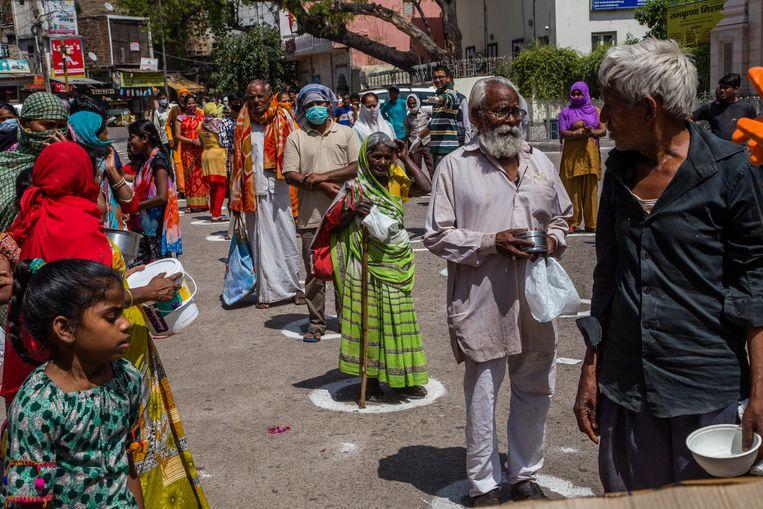 Voedsel wordt in de hoofdstad New Delhi uitgereikt door mensen 1,5 meter van elkaar plaats te laten nemen.   Beeld Getty Images
