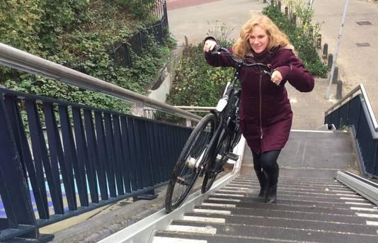 Wethouder Harriët Tiemens neemt de nieuwe fietsgoot in gebruik naast de trap vanaf de Hezelpoort naar de Snelbinder.
