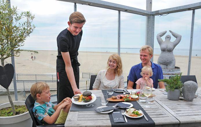 Het gezin Riemersma bestelt hetzelfde als wij: de Our Seaside plank en een visburger. Ober Sebas Molewijk serveert de lekkernijen.