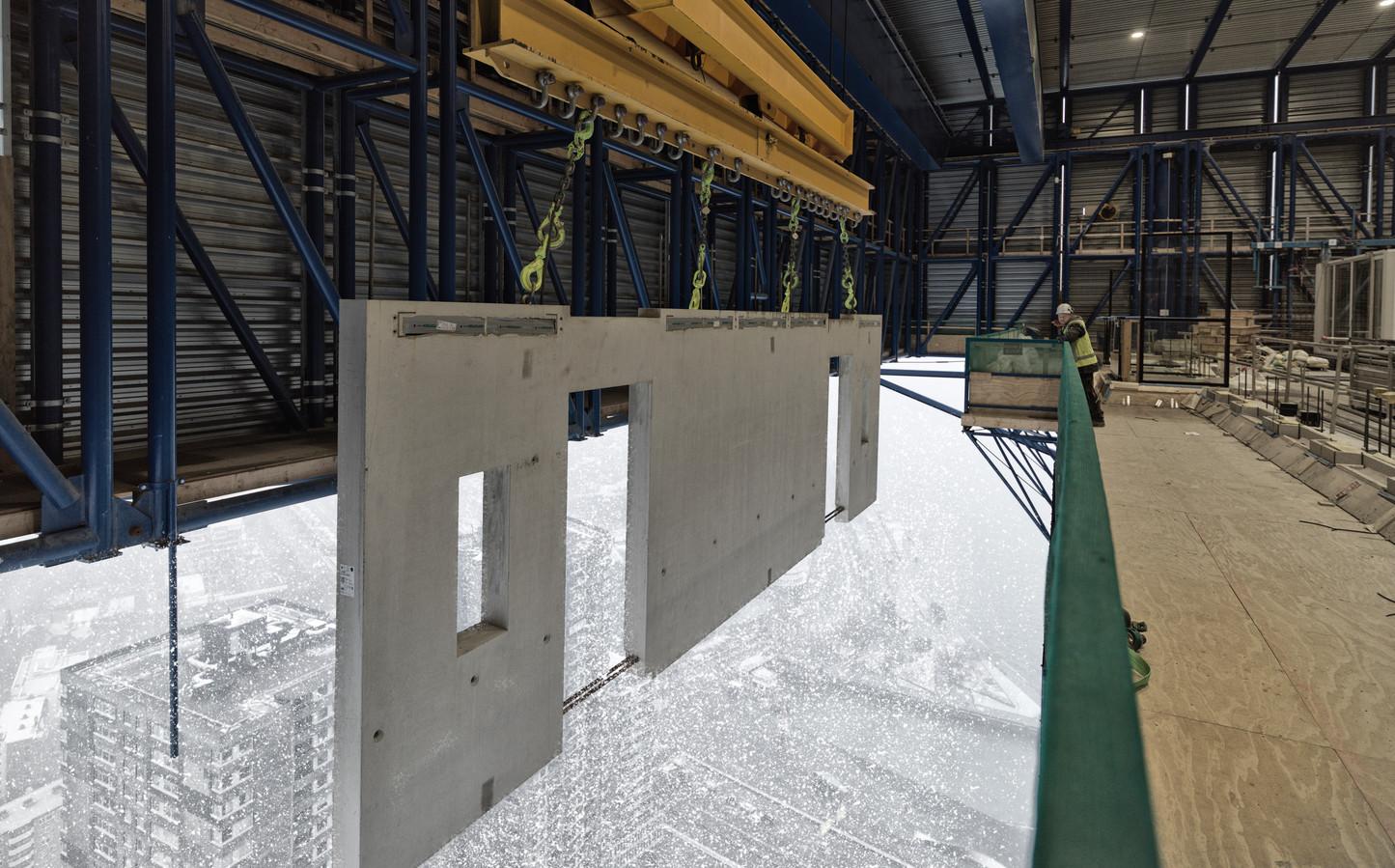 Byldis bouwt aan de 215 meter hoge toren van project De Zalmhaven in Rotterdam. Complete in de fabriek geproduceerde gevelelementen worden naar boven gehesen om te worden gemonteerd.