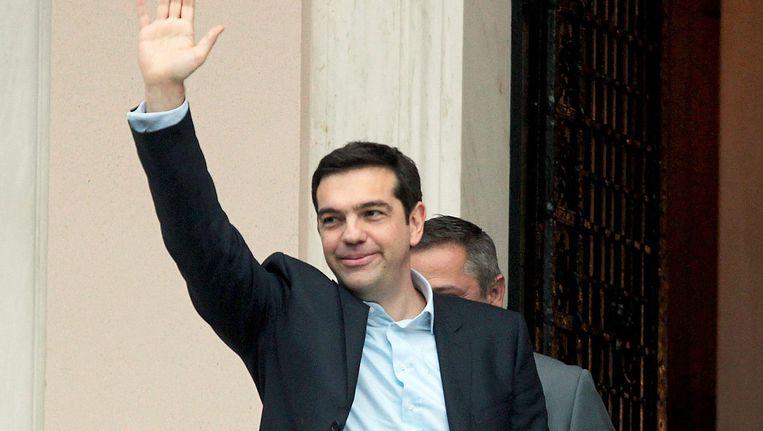 Alexis Tsipras, de leider van de linkse partij Syriza en kersverse premier van Griekenland zwaait toeschouwers en media toe. Beeld EPA