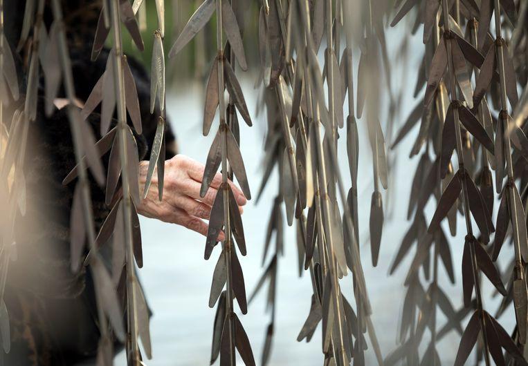 Een vrouw raakt van de Emanuel Gedenkboom aan, die in de  tuin van een synagoge in Boedapest staat. Op de metalen bladeren van het monument in de vorm van een treurwilg staan de namen van Hongaarse Joden die in de Tweede Wereldoorlog zijn omgebracht.  Beeld EPA