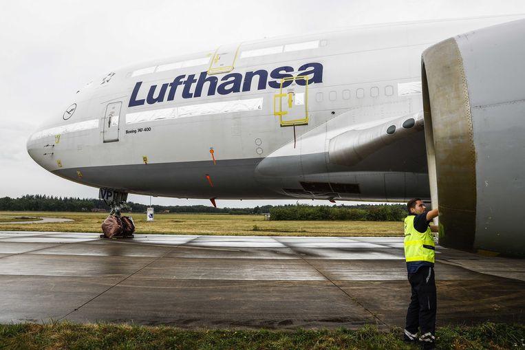 Een medewerker van Lufthansa Technik voert inspectie's uit aan geconserveerde Boeing 747-400's van Lufthansa op Twente Airport. Beeld ANP
