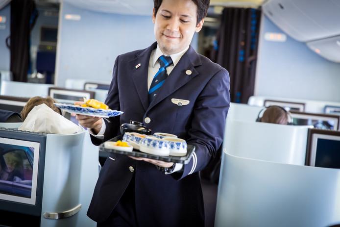 Het cabinepersoneel serveert de maaltijden van een dienblad. Foto KLM
