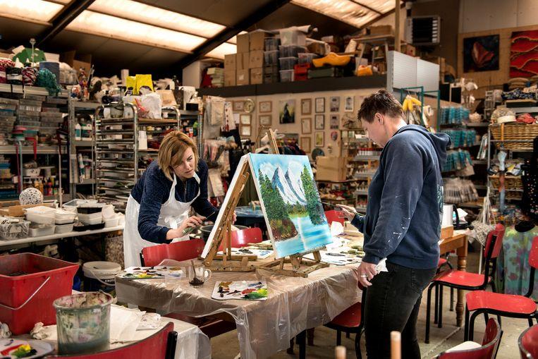 Anna van Leeuwen (links) aan het werk tijdens de Bob Ross-cursus.  Beeld Eva Faché