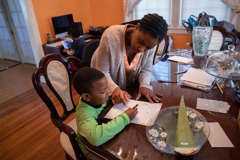 Geri Andre-Major helpt haar zoon Max (5) met het huiswerk.   Beeld AFP