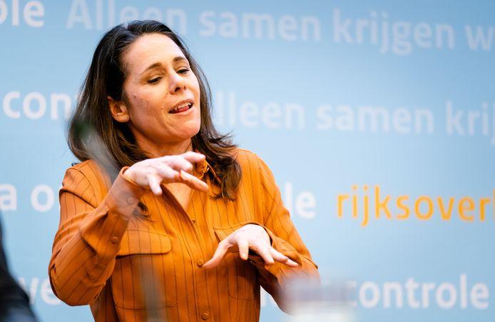Gebarentolk Irma Sluis maakt het hamstergebaar tijdens de persconferentie na afloop van het overleg van het crisisteam van het kabinet over de coronacrisis in december.