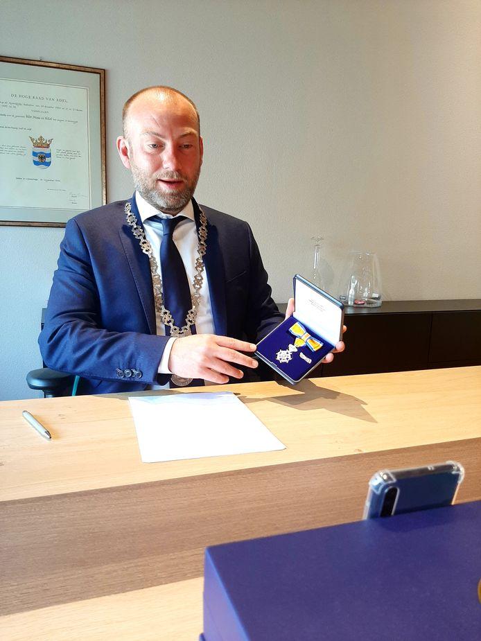 Burgemeester Vincent van Neerbos van West Maas en Waal belt met een gedecoreerde via een videocall.