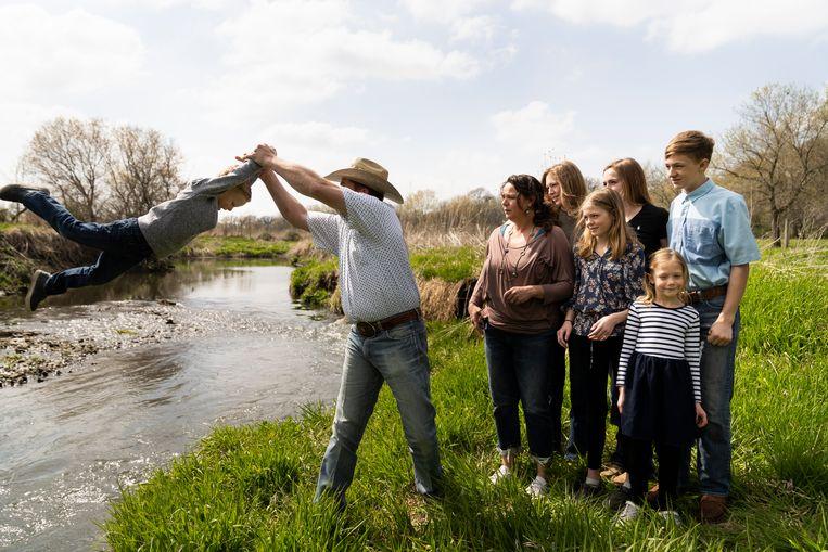 Justin Daugherty doet alsof hij zijn jongste zoon het water ingooit. Beeld Lauren Justice