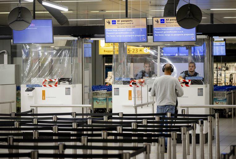 Paspoortcontrole op Schiphol. De marechaussee controleert ook de negatieve coronatestuitslagen voor reizigers vanuit en naar Nederland. Beeld ANP